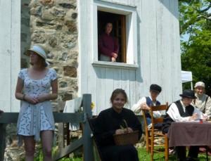 De gauche à droite : Clémence Léveillé (jeune fille d'aujourd'hui), à la fenêtre: Magalie Ouellet (Ulric). Assis : Isanne Morin (Émilie Brouillette, mère), John Goedkoop (Honorius), William Morin (Ozias), Camille Auger-L'Espérance (Origène).